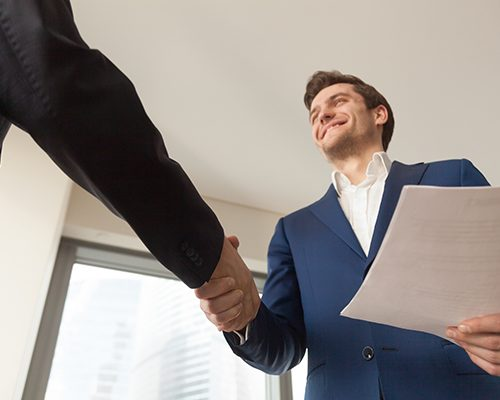 Satisfied businessman with business documents shaking hand to partner, making deal after reviewing terms of contract, offering profitable project to investor, happy of partnership, welcoming client